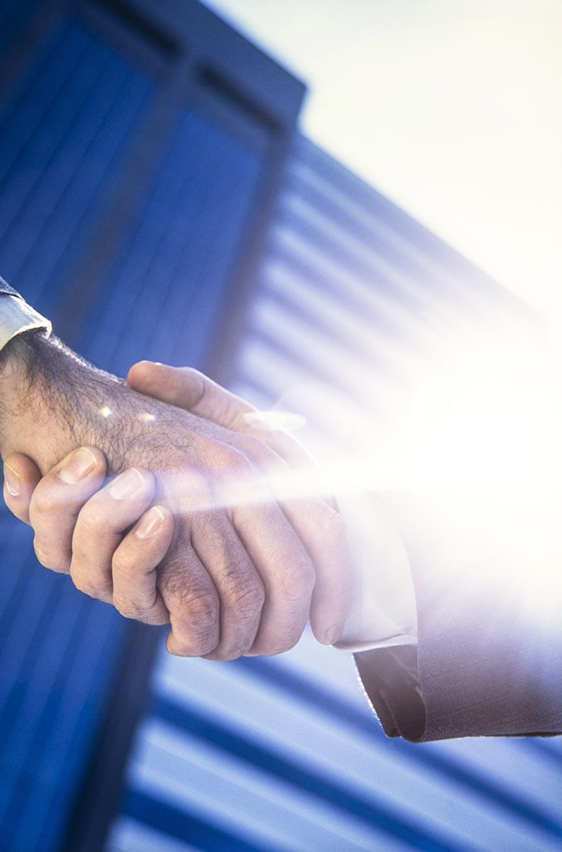 Free stock photo Businessmen shaking hands against a background of office building