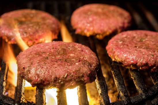 Free stock photo Hamburgers just beginning to cook over a fire on a charcoal grill