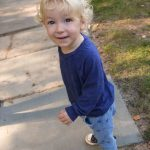 Free stock photo Portrait of boy smiling while standing on footpath in park