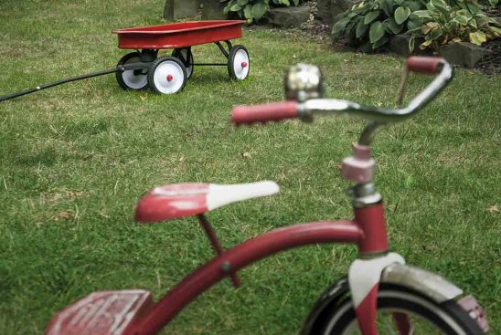 Free stock photo Red wagon and bicycle on grass