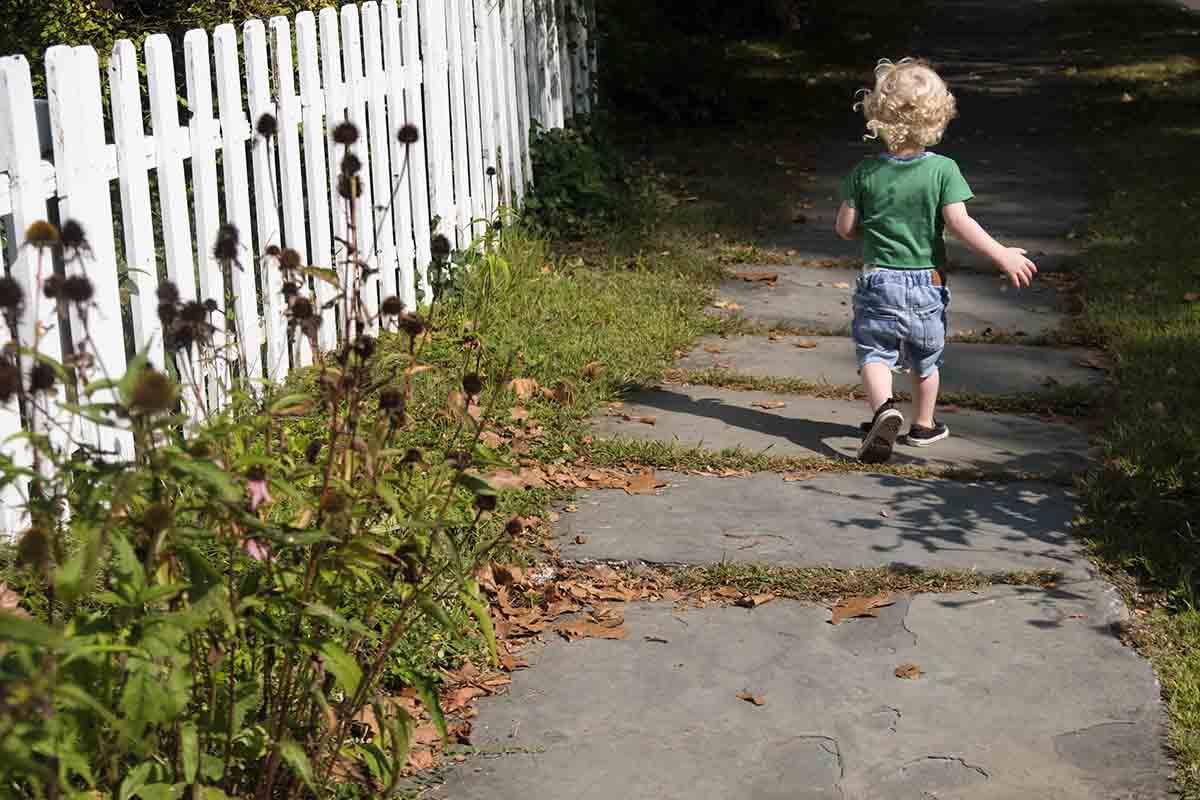Free stock photo Rear view of boy walking on a sidewalk