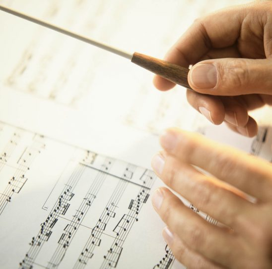 Free stock photo A conductor's hands waving a baton over a page of music