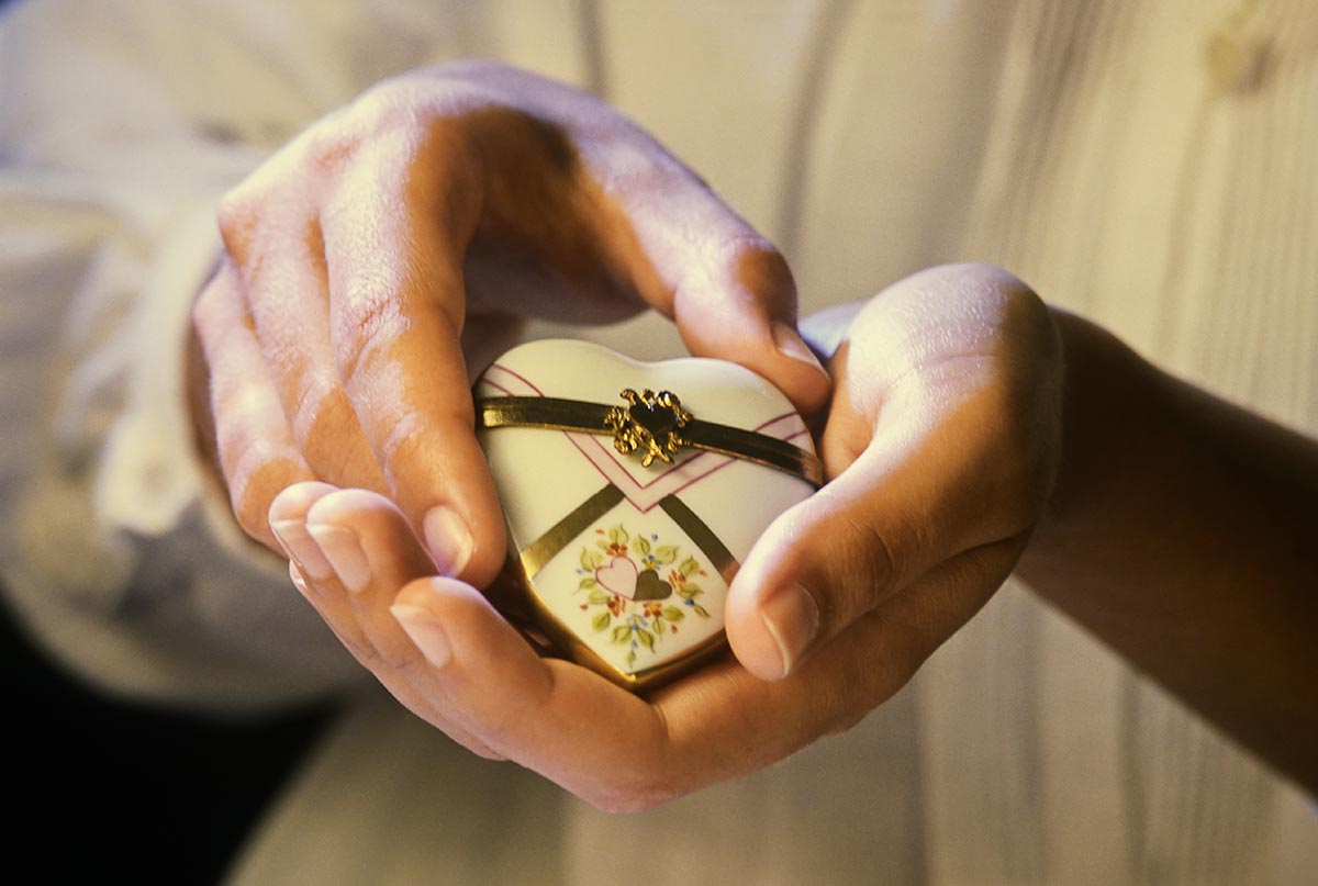 Free stock photo Woman's hands holding a heart locket