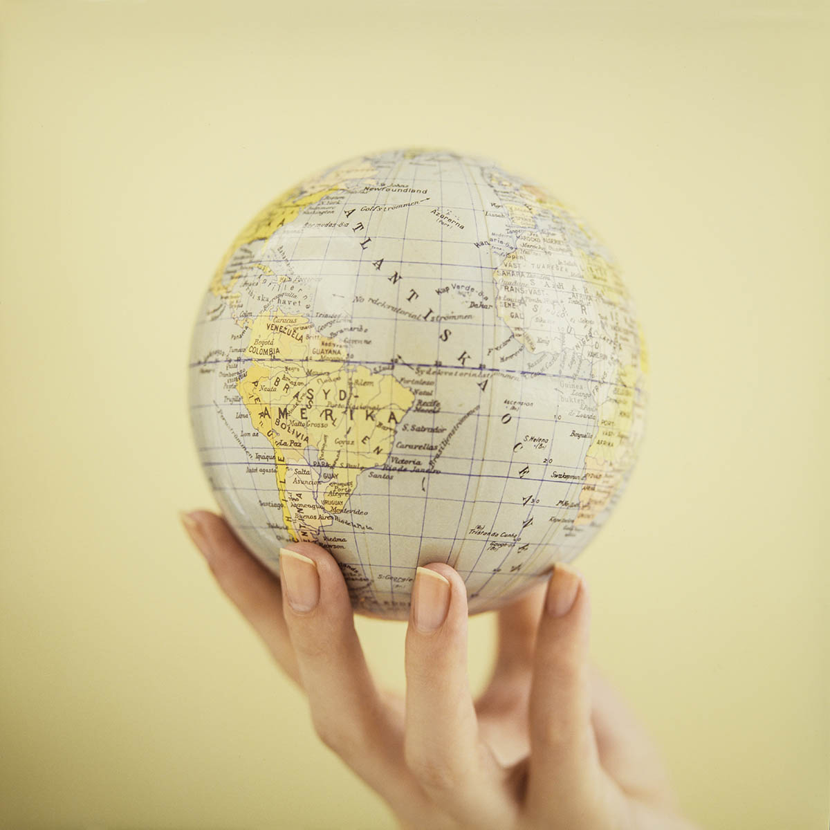 Free stock photo Woman's hand holding up a globe