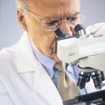 Free stock photo Medical technician looking into a microscope