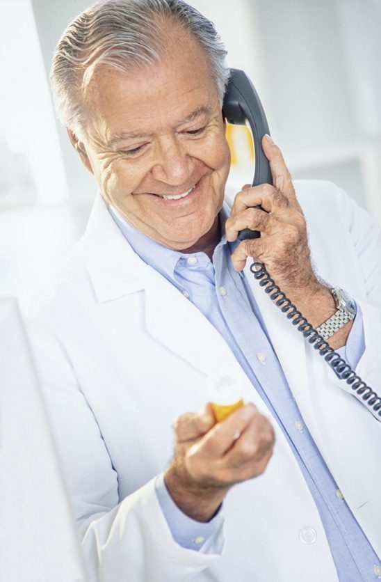 Free stock photo Pharmacist looking a pill box while talking on the phone