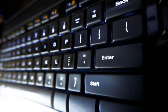 Free stock photo Black computer keyboard with Enter key and light flare
