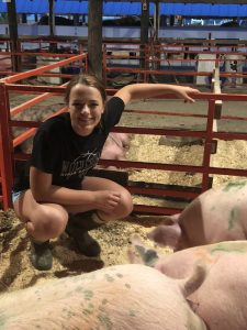 teen girl kneeling by pigs in a pen