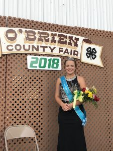 teen girl in formal dress, sash and crown holding flowers in front of a backdrop that reads O'Brien County Fair