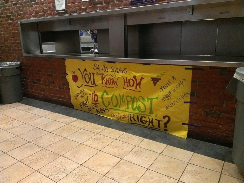 A large yellow sign was hung by the Landfill, Recycling, and Composting receptacles in the Dining Commons created by the students who launched composting efforts on campus to informed students about how to compost their food waste.