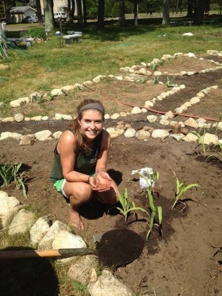 Christine Moodie (2015) designed our permaculture garden as a thesis project.  In this photo she sees her design to fruition, helping to plant corn in the Three Sisters (corn, beans and squash) section of the garden at the farm.