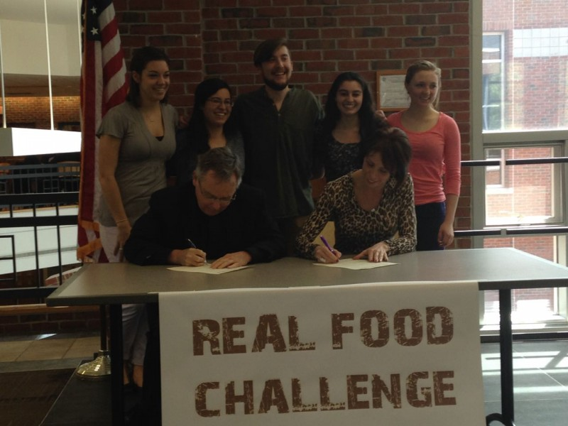 College President, Rev. John Denning, C.S.C, and Vice President for Student Affairs, Pauline Dombrowski, sign a committment to The Real Food Challenge. Happy Students stand behind them, smiling at this accomplishment.