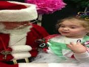 A little girl talking to Santa