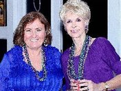 Paula Rosen and Pat Schmader celebrate at Mardi Gras dinner dance.
