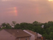 rainbow in clouds as sun setting