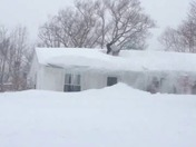 man in our local area cleaning snow over his house