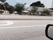 Truck hauling excavator crashes through parking lot at school hitting cars barle