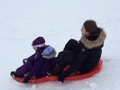 Lily and Jada sledding down the hill