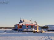 Blue houseboat near an island on Yellowknife Bay in Great Slave Lake