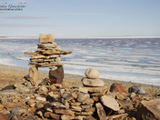 Inukshuk or Inuksuk on a rocky beach with ice on the ocean in late June in the h
