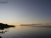 Beautiful sunrise over an arctic lake with fog on the horizon and sun peaking ov