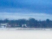 Coal barge and boat going through fog on The Ohio River