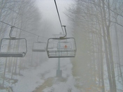 Lonely skier in a ski lift chair.