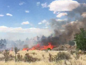 Albuquerque foothills brush fire breaks out between homes.