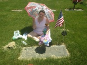 Heather Willcox at her grandmother and grandfather grave putting flowers on it.
