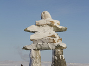 Inukshuk or Inuksuk landmark covered in snow found on a hill in the community of Rankin Inlet