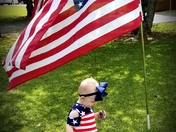18 month old Ellison Ray stands under the American flag