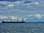 Cargo ship and a paddle board.