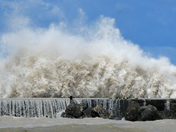 Huge wave explodes on contact with pier.