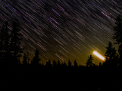 Moon setting and colourful stars in the boreal forest at Riding Mountain National Park