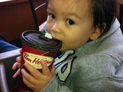 Teething Baby with Tims Decaf Coffee Cup