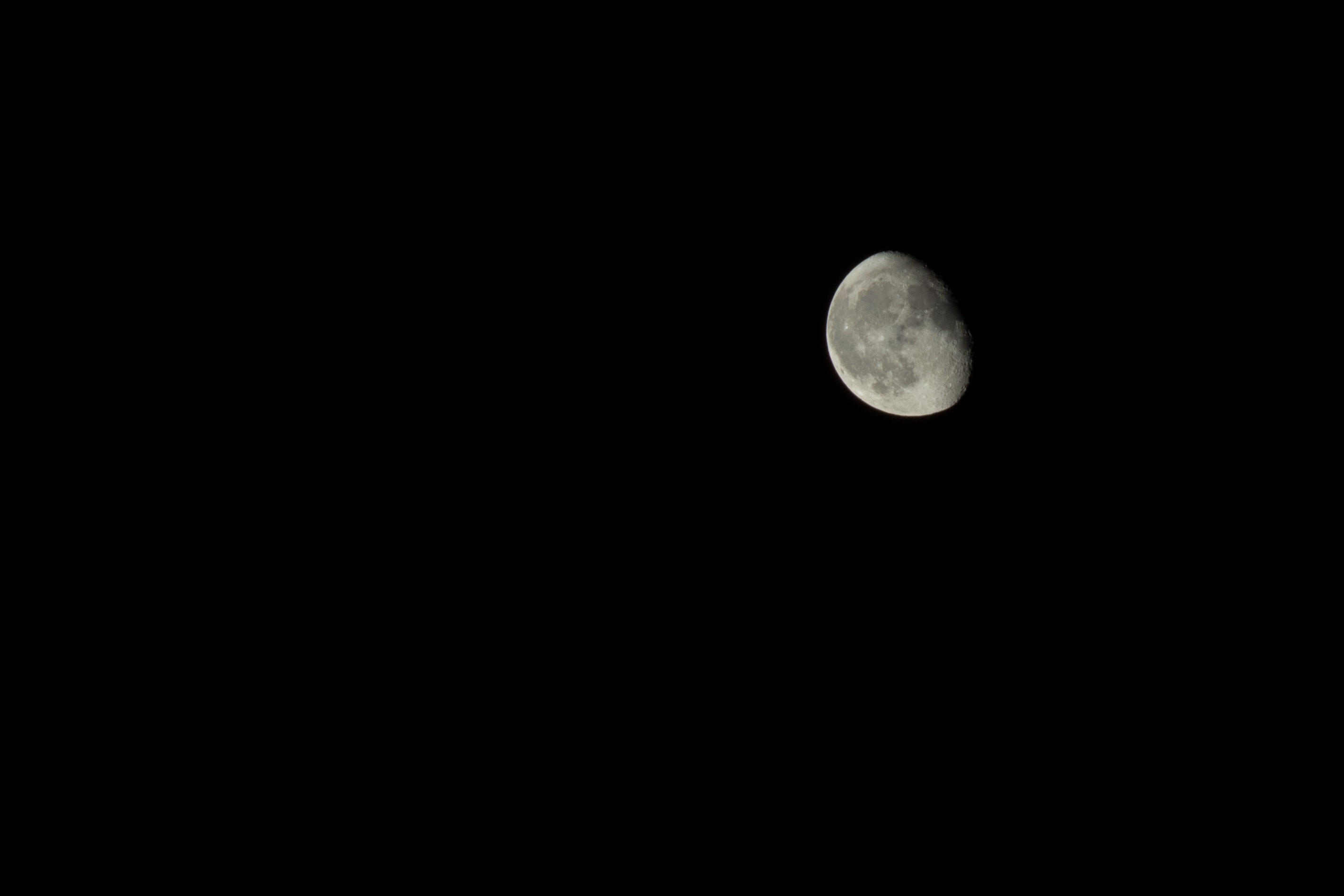 Gibbous moon against a pitch-black sky