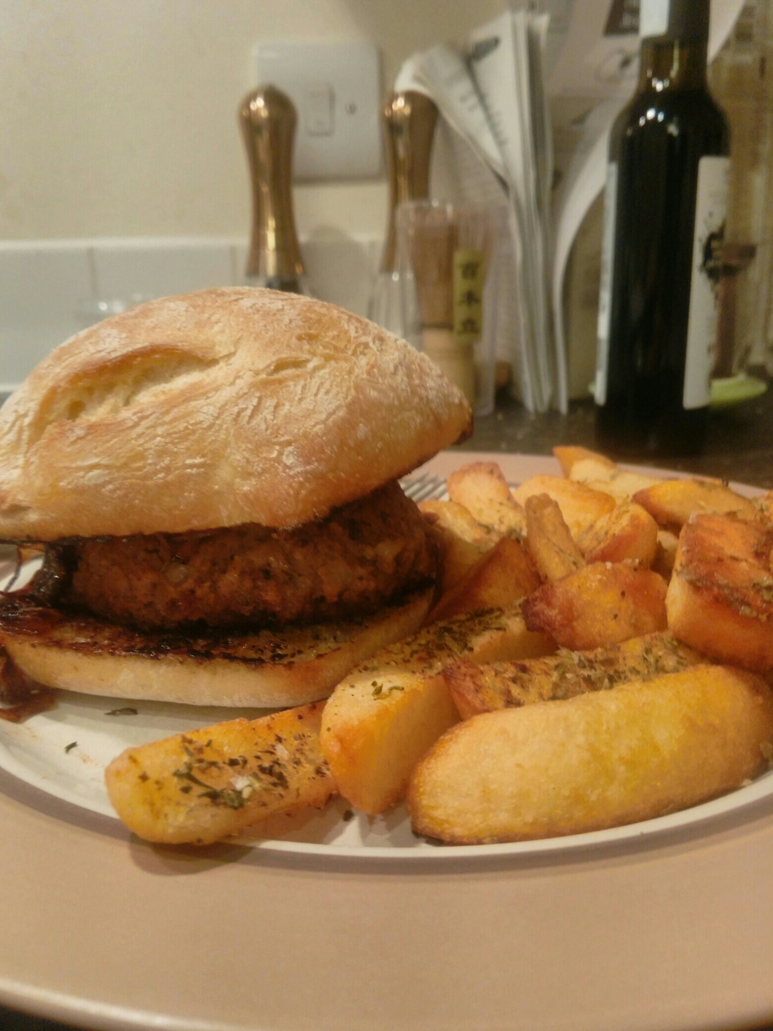 Burger in a bun and chips on a plate
