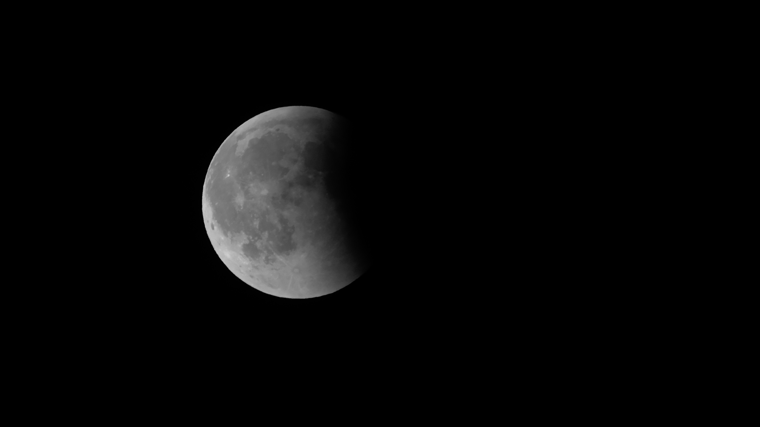 Full moon roughly one-third obscured by Earth's shadow