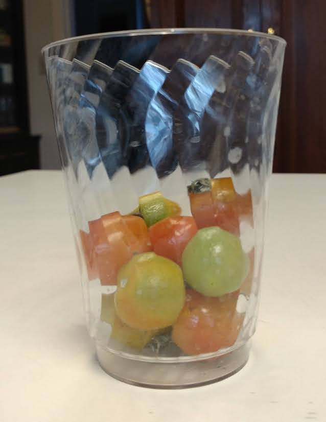 photo: cherry tomatoes in various stages of ripening, in a clear plastic cup