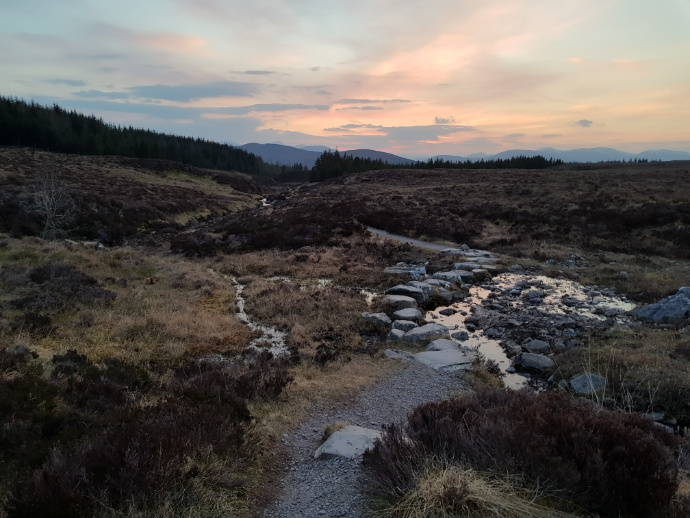 Path with stepping stones across a moorland stream, mountains in the distance