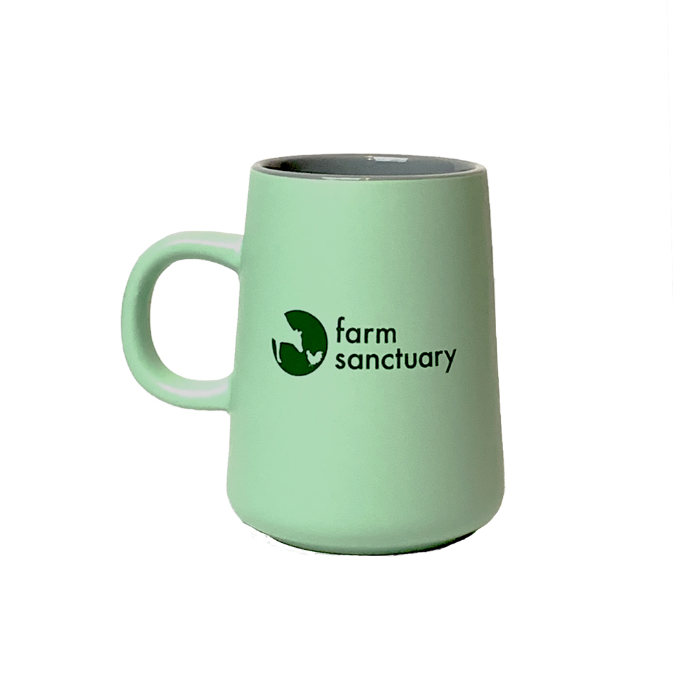 Light green and gray mug tapered at the top with the Farm Sanctuary logo