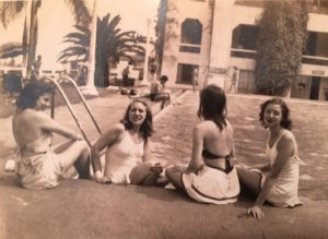 Four students sitting at a pool