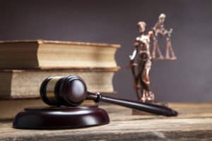 Criminal Justice degree books, gavel and Lady Justice statue