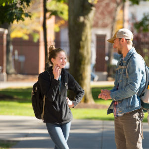 Male and female student talking outside on campus