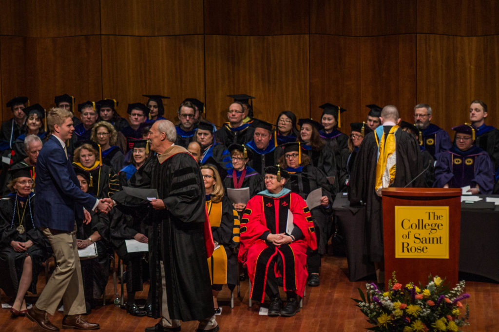 Student receiving award from Interim Dean Michael Mathews at the Honors Convocation on March 24, 2018.