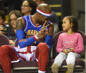 "Tay ""Firefly"" Fisher with a fan at a Harlem Globetrotters game"