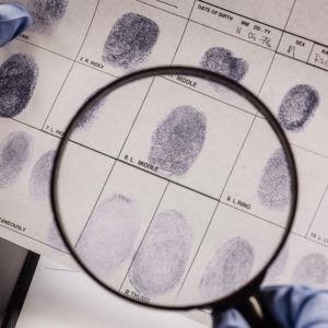 magnifying glass inspecting finger prints