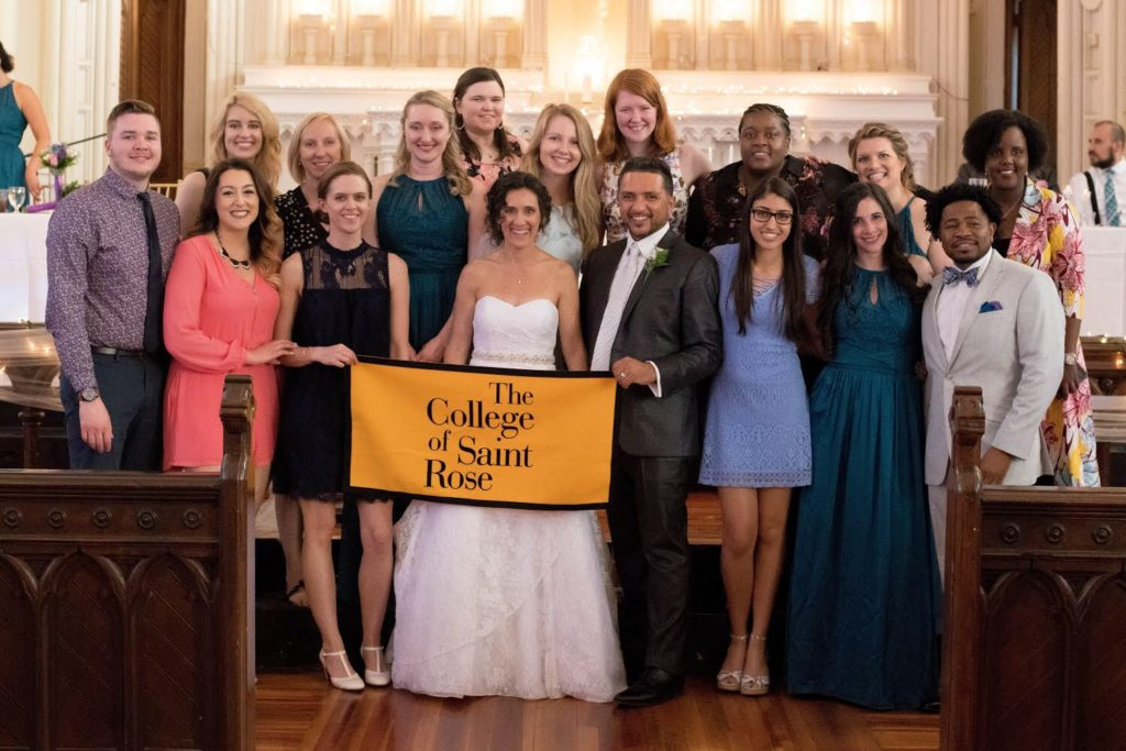 Rachel Deeb Gutierrez '02, G'04 sent a lovely photo of Saint Rose alums who attended her wedding to Victor Gutierrez in June 2018, at her wedding with Saint Rose alums and Saint Rose banner