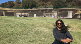 Guadalupe Chavez sitting on the grass visiting the Great Pyramids of Cholula, a small Pueblo magico outside of the state of Puebla