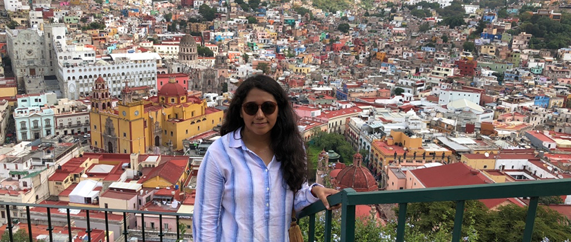 Guadalupe Chavez, standing on a hill above a Mexican city